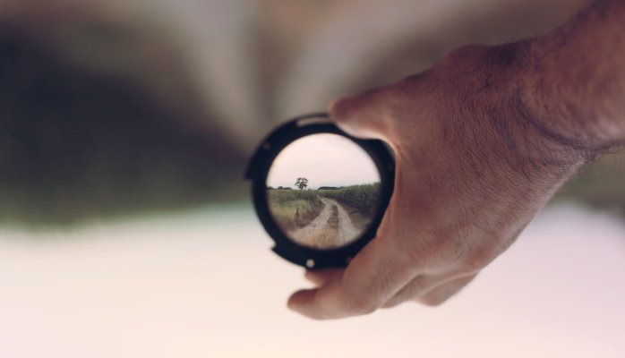 Man holding a lens that shows a dirt road right side up while the background is upside down