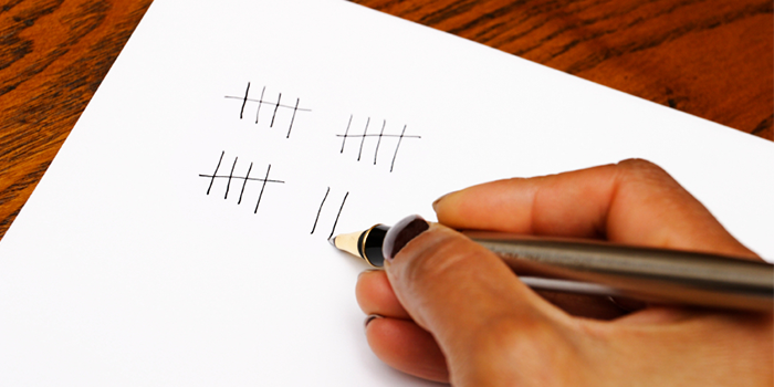 Woman's hand holding a pen writing tally marks on a piece of white paper