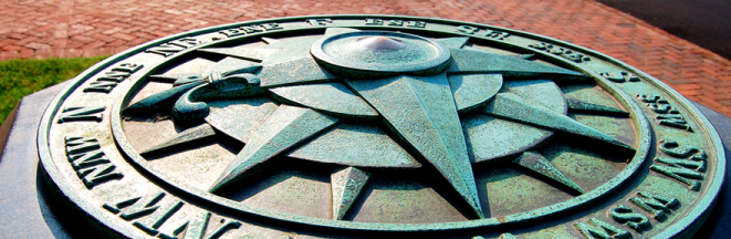 Oxidized metal compass statue